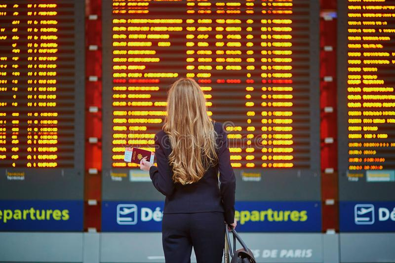 Femme avec le bagage de main dans le terminal d'aéroport international, regardant le conseil de l'information photos stock
