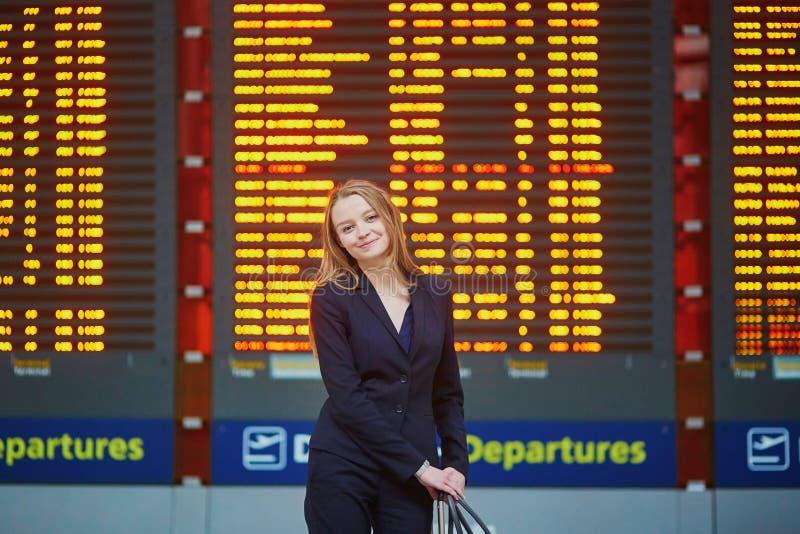Femme avec le bagage de main dans le terminal d'aéroport international, regardant le conseil de l'information images libres de droits