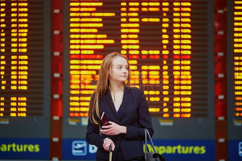 Femme avec le bagage de main dans le terminal d'aéroport international, regardant le conseil de l'information photos stock