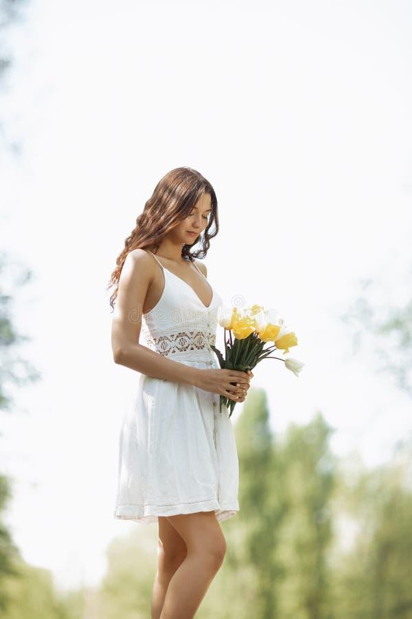 Femme avec le bouquet des fleurs de ressort dehors photos libres de droits