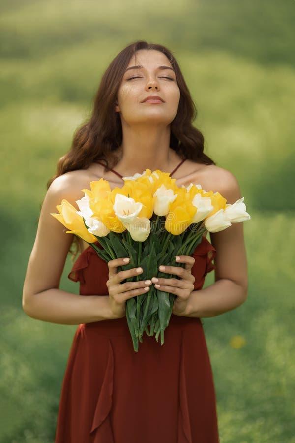 Femme avec le bouquet des fleurs de ressort dehors photos stock