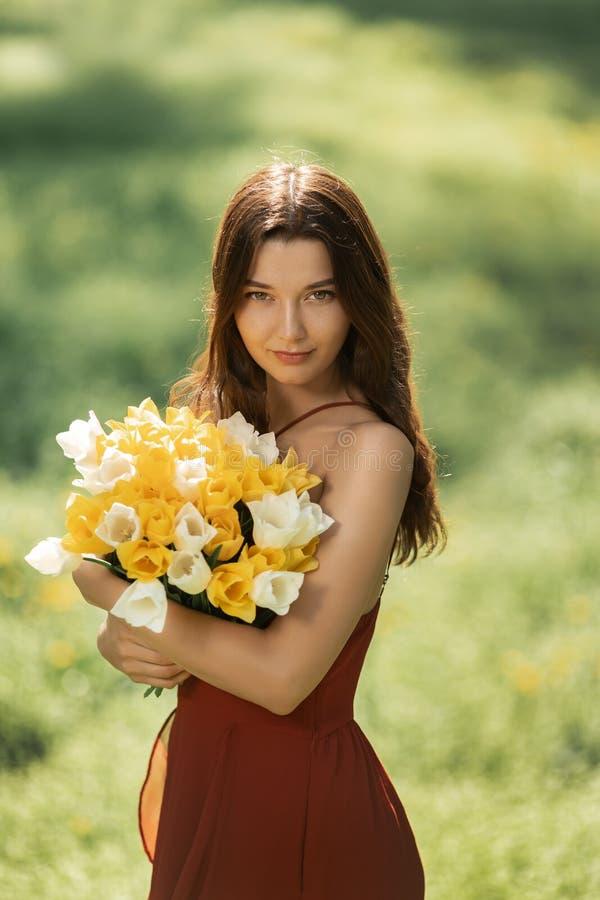 Femme avec le bouquet des fleurs de ressort dehors images libres de droits