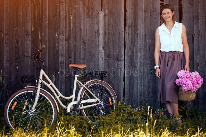 Femme avec le bouquet des pivoines et de la bicyclette photos libres de droits