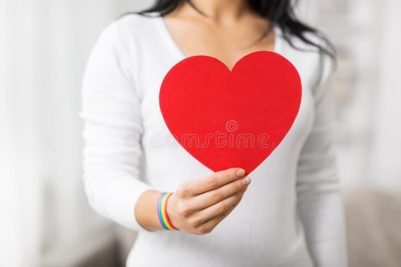 Femme avec le bracelet gai de conscience tenant le coeur photo stock