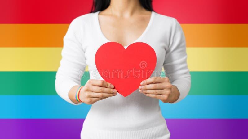 Femme avec le bracelet gai de conscience tenant le coeur images stock