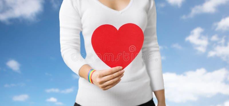 Femme avec le bracelet gai de conscience tenant le coeur photos libres de droits