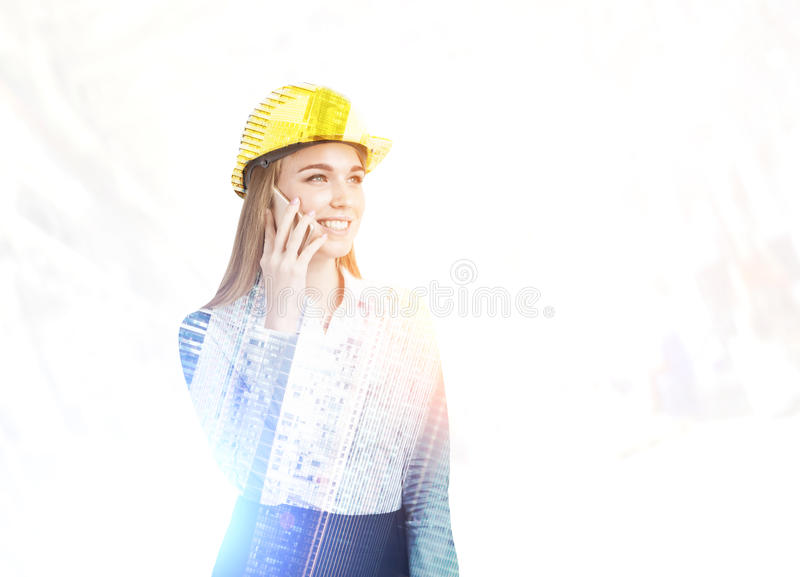 Femme avec le casque antichoc au téléphone, vue de ville photo libre de droits