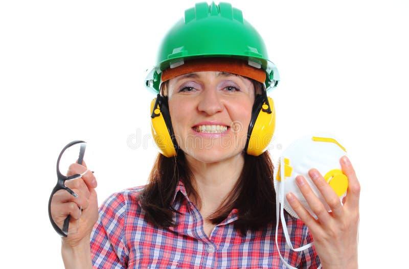 Femme avec le casque de protection, les écouteurs, le masque et les lunettes photos stock
