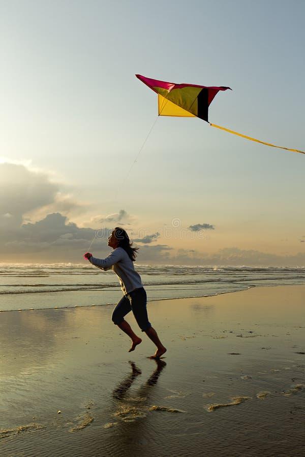 Femme avec le cerf-volant à la plage photo stock