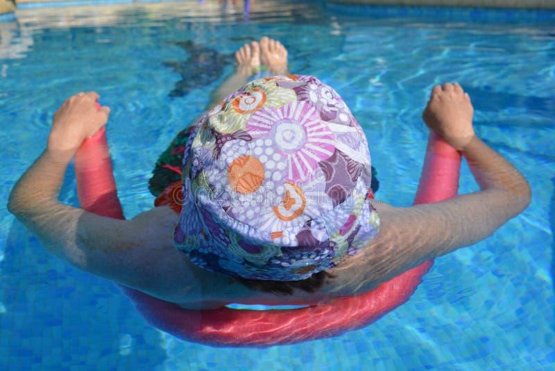 Femme avec le chapeau détendant dans une piscine, maintenant frais photographie stock