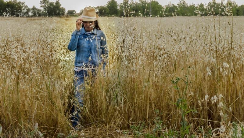 Femme avec le chapeau dans un domaine de blé, femme heureuse images stock
