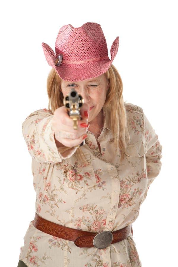 Femme avec le chapeau de cowboy rose dirigeant le pistolet photographie stock libre de droits