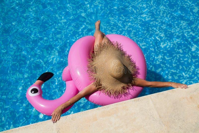 Femme avec le chapeau de paille dans la piscine avec un flamant rose gonflable photo libre de droits