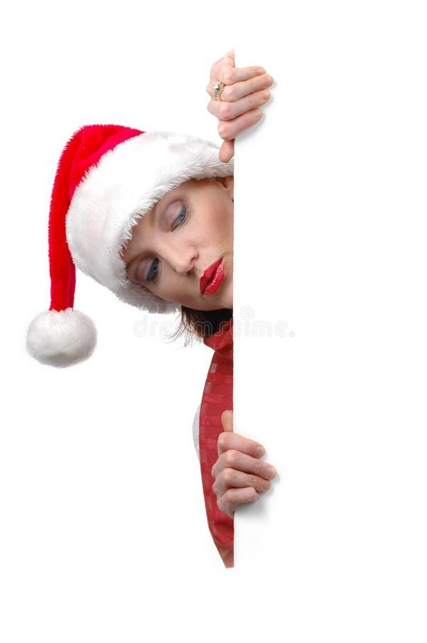 Femme avec le chapeau de Santa retenant le signe blanc photo stock