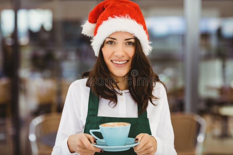 Femme avec le chapeau de Santa tenant le café photographie stock