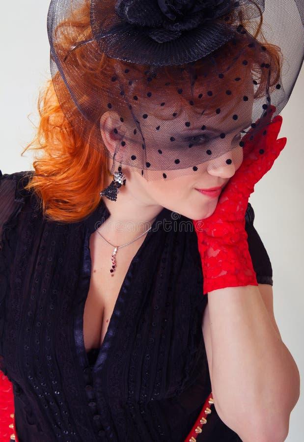 Femme avec le cheveu rouge dans le chapeau noir images stock