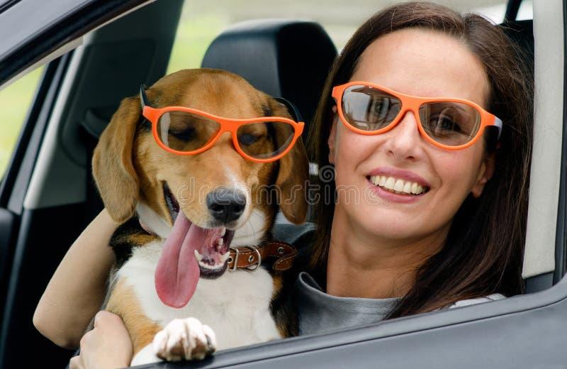 Femme avec le chien de briquet dans une voiture photographie stock