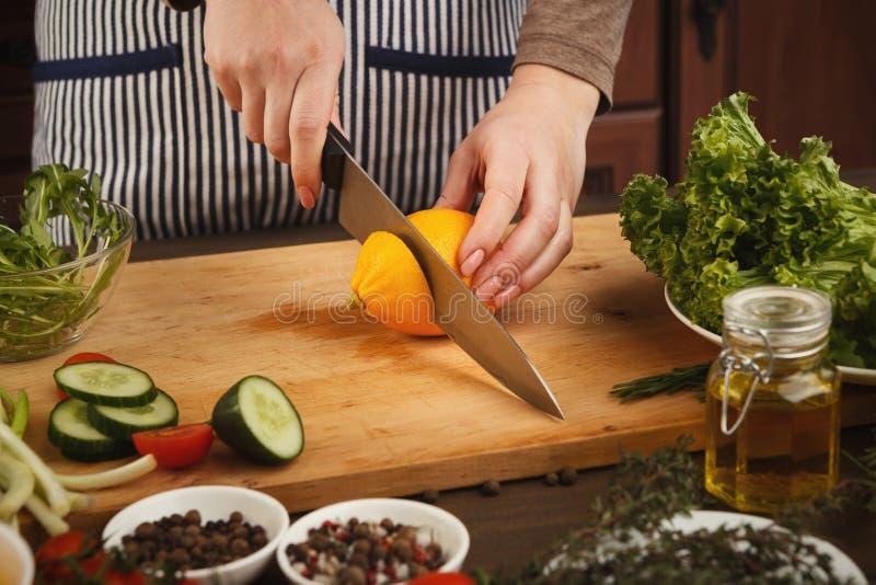 Femme avec le citron de coupe de couteau sur le conseil en bois image libre de droits