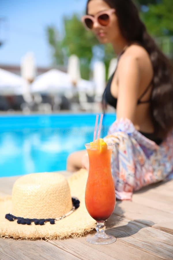 Femme avec le cocktail et le chapeau de paille près de la piscine photographie stock libre de droits