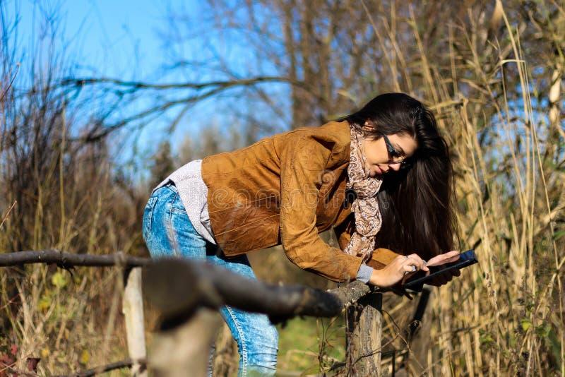 Femme avec le comprimé numérique en nature photographie stock libre de droits