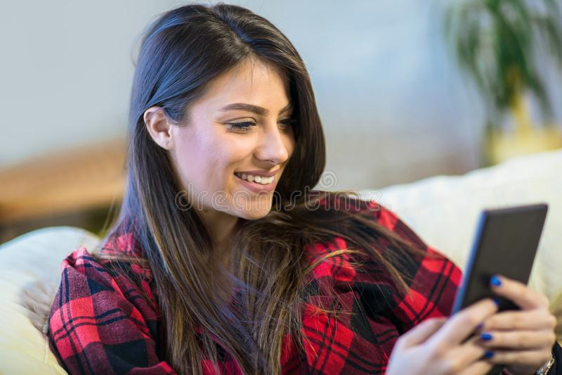 Femme avec le comprimé numérique se reposant sur le sofa à la maison photo stock