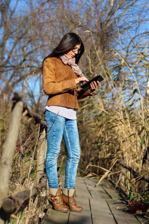 Femme avec le comprimé numérique sur le vieux pont en bois photographie stock libre de droits