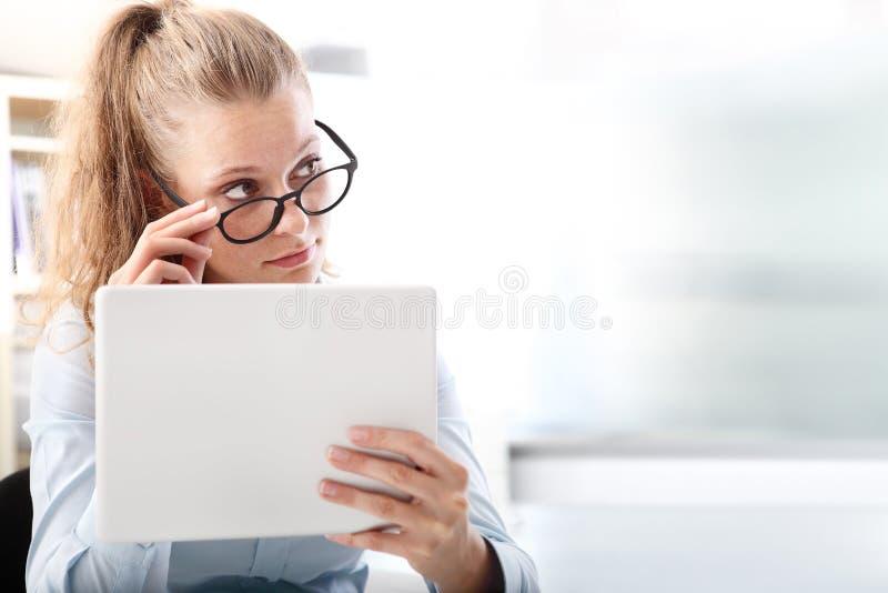 Femme avec le comprimé recherchant au côté photos libres de droits