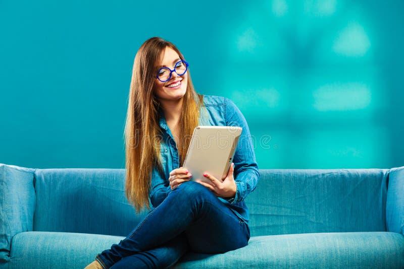 Femme avec le comprimé se reposant sur la couleur de bleu de divan photos stock