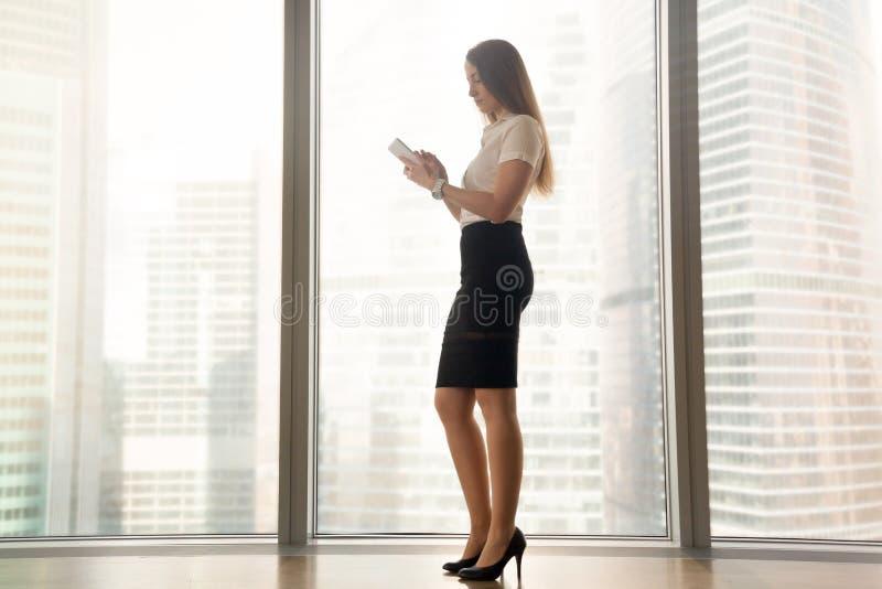 Femme avec le comprimé sur le fond du paysage de ville image stock
