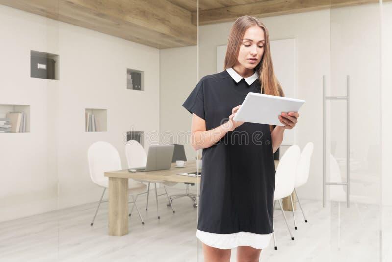 Femme avec le comprimé tenant la salle de conférence proche avec des murs de verre illustration libre de droits