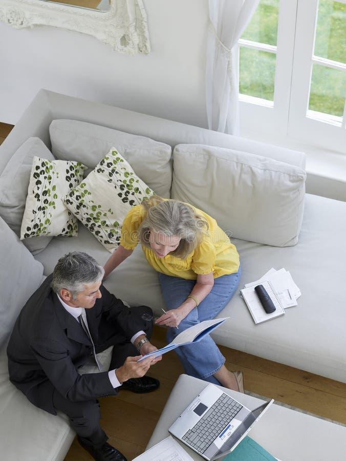 Femme avec le conseiller financier sur le sofa images stock