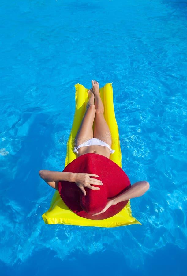 Femme avec le corps bronzé parfait se trouvant sur le matelas d'air jaune dans t photos libres de droits
