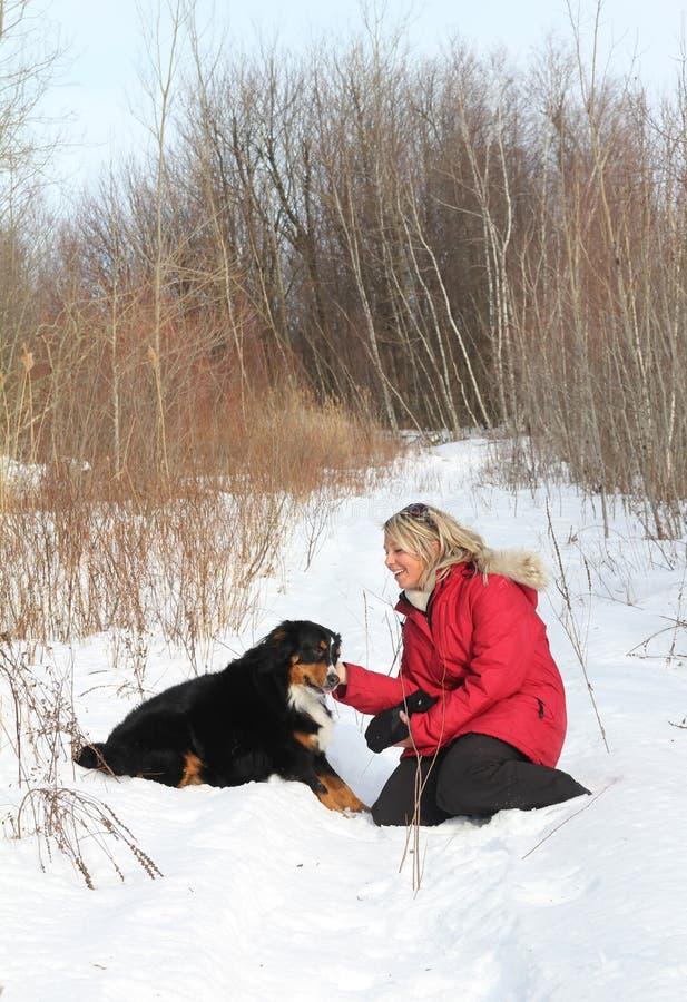 Femme avec le crabot dans la neige images libres de droits