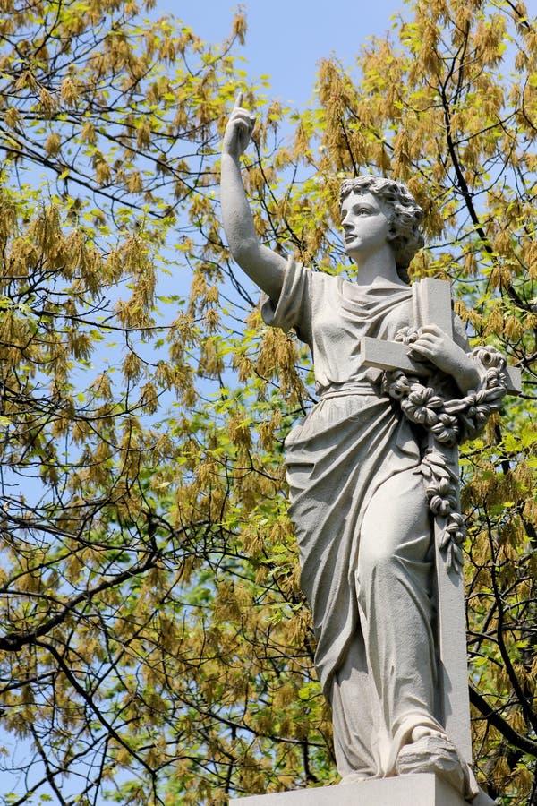Femme avec le crucifix et la statue florale de guirlande images stock