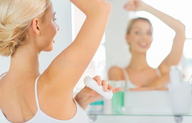 Femme avec le désodorisant antisudoral à la salle de bains photos stock