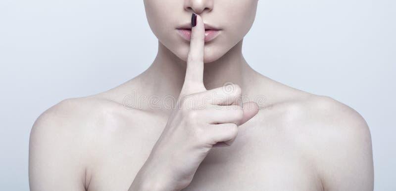 Femme avec le doigt sur des lèvres photos stock