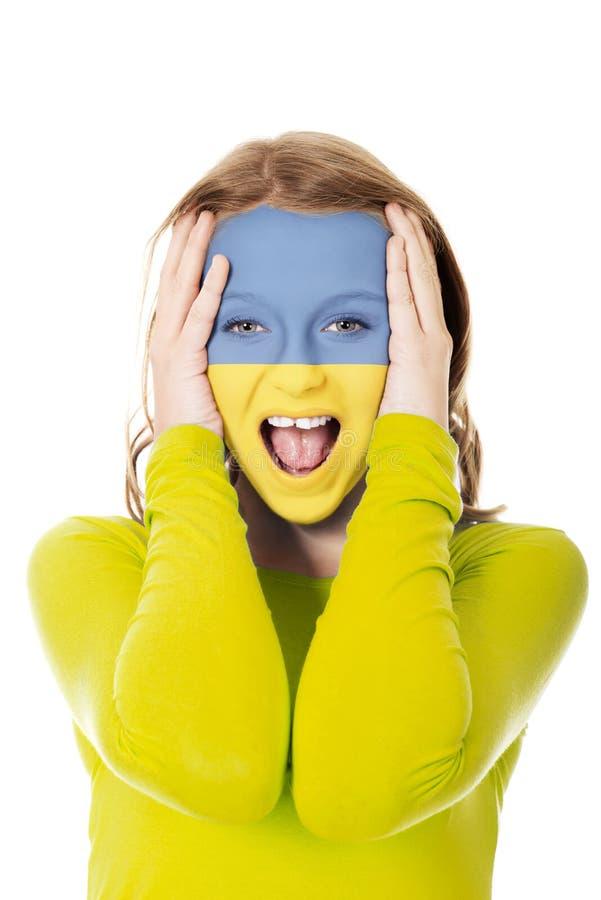 Femme avec le drapeau de l'Ukraine sur le visage photos stock