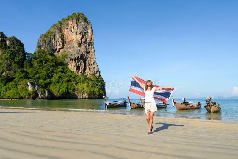 Femme avec le drapeau de la Thaïlande appréciant le voyage à la plage de Krabi image libre de droits