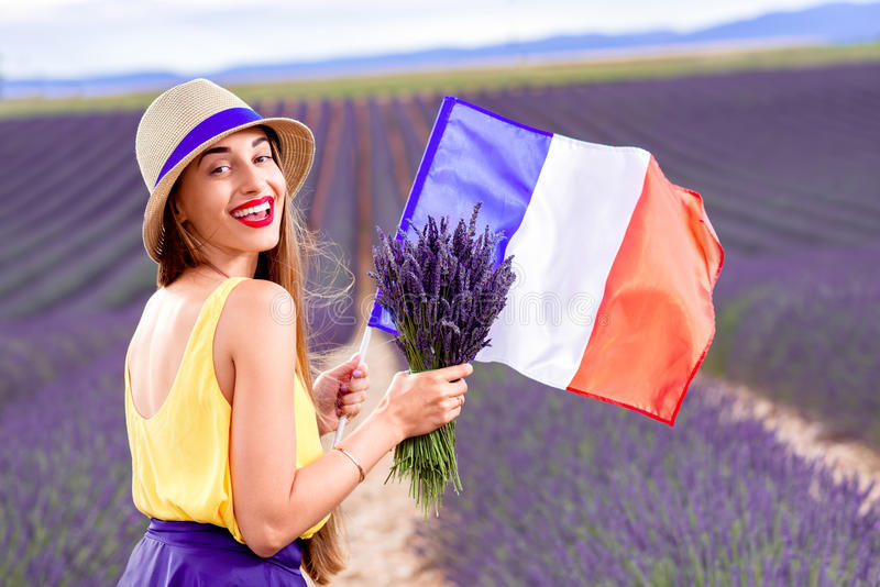 Femme avec le drapeau français dans le domaine de lavande photographie stock libre de droits