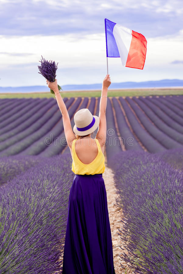 Femme avec le drapeau français dans le domaine de lavande images stock