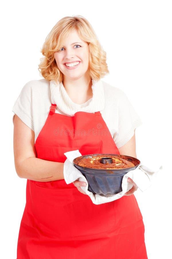 femme avec le gâteau de bundt et le tablier rouge images stock