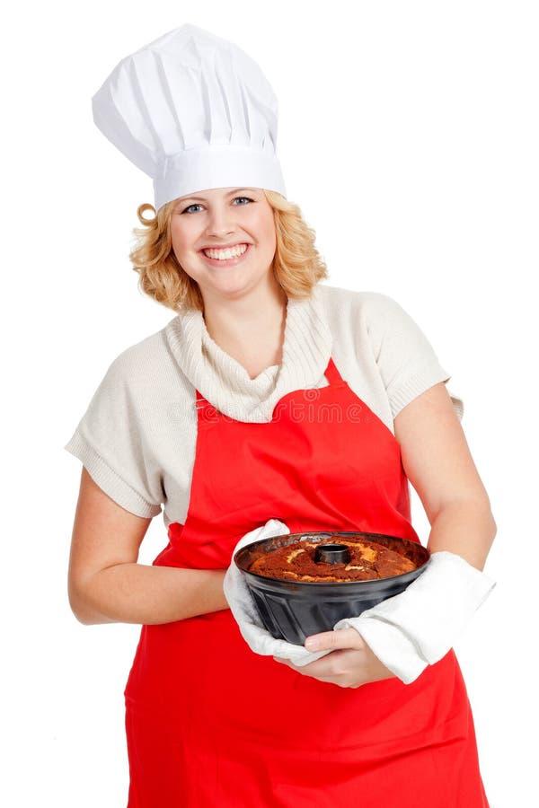 Femme avec le gâteau de bundt s'usant un tablier rouge images stock