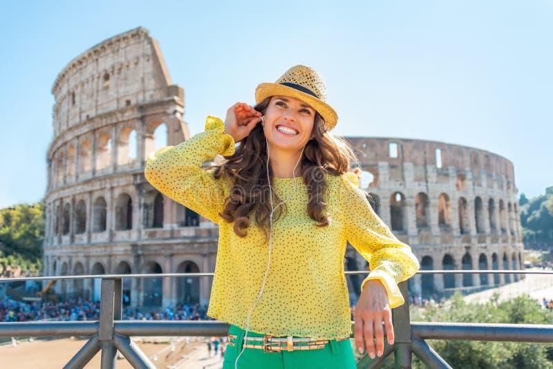 Femme avec le guide audio devant le colosseum photos stock