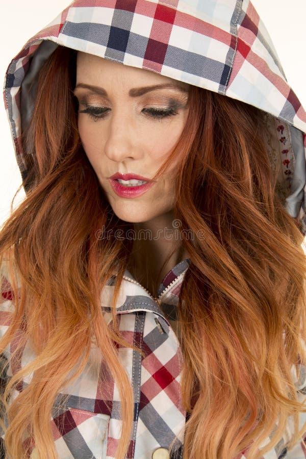 Femme avec le hairr rouge dans le regard étroit de capot de plaid vers le bas photo libre de droits