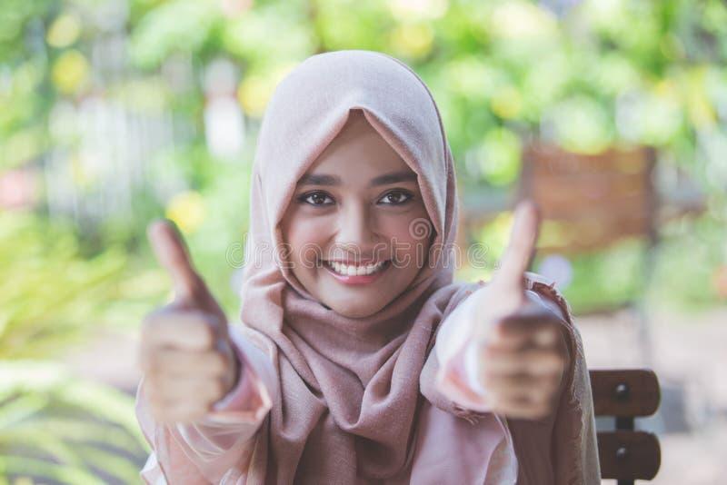 Femme avec le hijab montrant le pouce  photographie stock