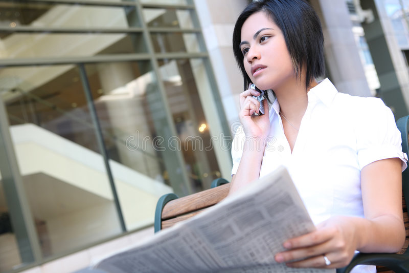 Femme avec le journal et le téléphone image stock