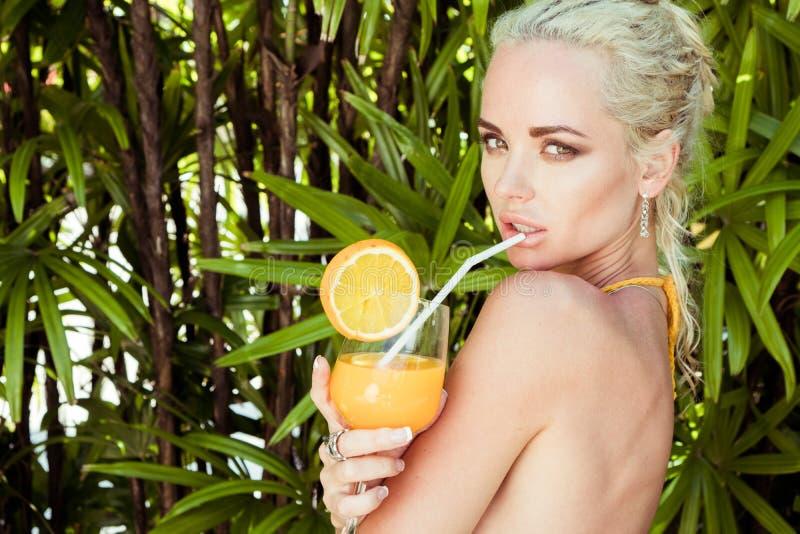 Femme avec le jus d'orange à l'hôtel de tourisme tropical image libre de droits