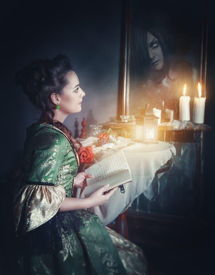 Femme avec le livre dans la rétro robe et le fantôme dans le miroir image libre de droits