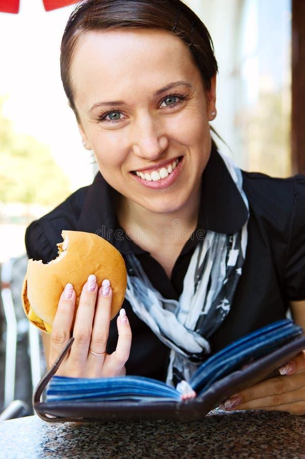 Femme avec le livre de relevé d'hamburger photographie stock libre de droits