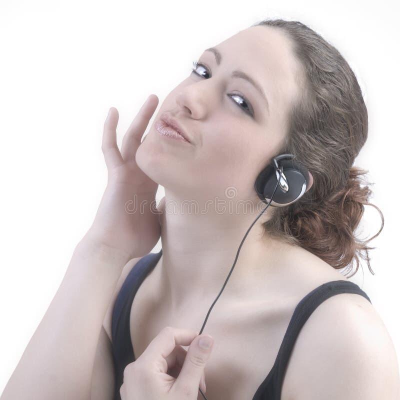 Femme avec le long cheveu bouclé avec des écouteurs photographie stock libre de droits